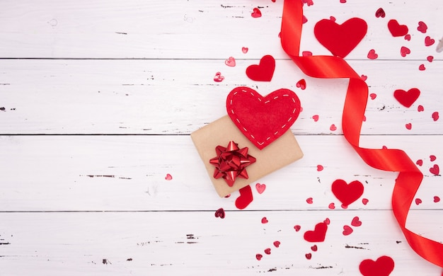 Regalo e cuori rossi su fondo di legno bianco, vista dall'alto. copyspace, un concetto di san valentino.