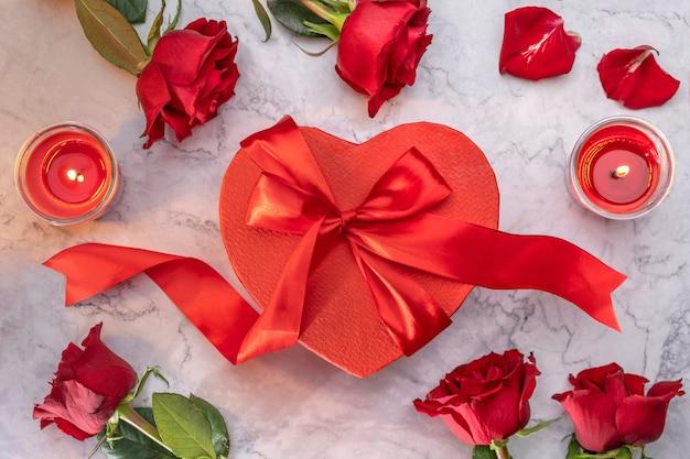 Confezione regalo rossa a forma di cuore con fiocco in raso circondato da rose e candele