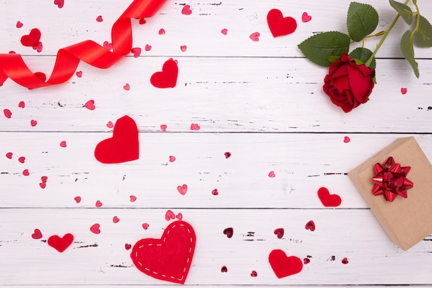 Regalo, rosa e cuori rossi su fondo di legno bianco, vista dall'alto. copyspace, un concetto di san valentino.