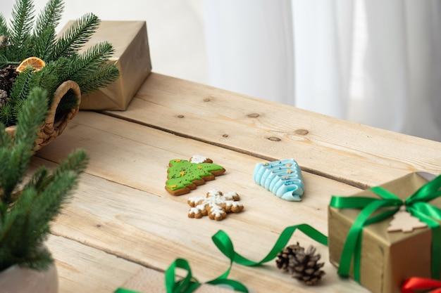 Regalo legato con un nastro, rami di pino e decorazioni su un tavolo di legno