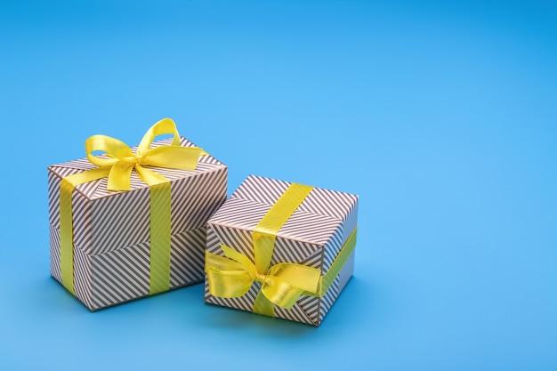 Regalo in due scatole, avvolto in carta vacanze e legato con nastro giallo con fiocco. una sorpresa per ogni vacanza ed evento.