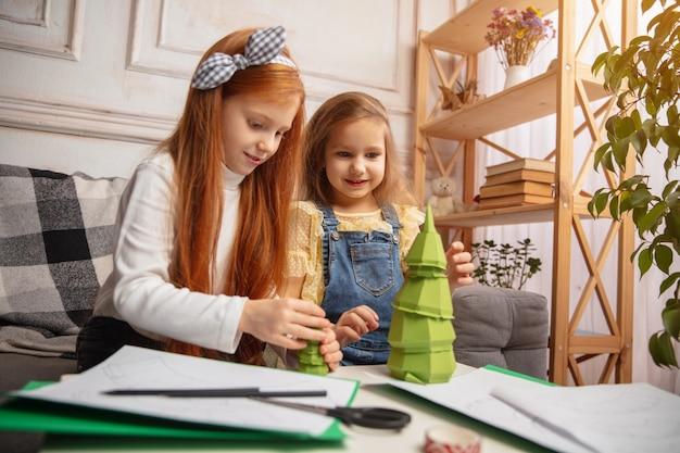 Regalo. due bambini piccoli, ragazze insieme nella creatività della casa. i bambini felici realizzano giocattoli fatti a mano per i giochi o per la festa di capodanno. piccoli modelli caucasici. infanzia felice, preparazione al natale.