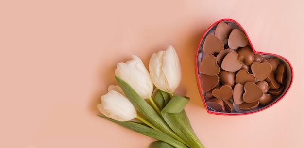 Regala fiori bianchi e caramelle in una scatola a cuore su uno sfondo rosa pallido. vista dall'alto. copia spazio. banner