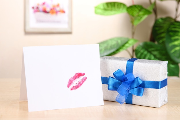 Regalo con carta per la persona amata sul tavolo sullo sfondo della stanza