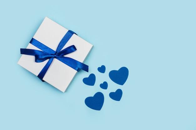 Un regalo con cuori di carta blu su sfondo azzurro