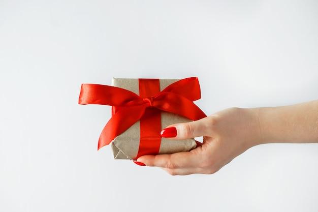 Regalo con un nastro rosso in mano su uno sfondo bianco. fare un regalo per san valentino