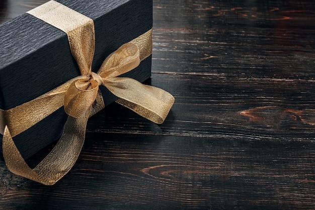 Un regalo avvolto in carta nera e legato con un nastro d'oro
