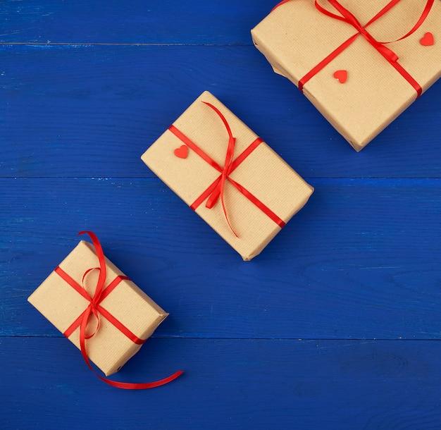 Regalo avvolto in carta kraft marrone e legato con un sottile nastro rosso su uno sfondo di legno blu