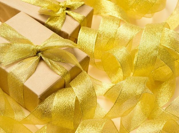 Regalo avvolto in carta marrone su uno sfondo di nastro dorato ritorto, sfondo festivo, vista dall'alto