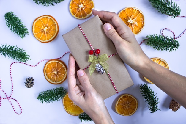 Regalo avvolto in carta kraft in mano su uno sfondo bianco con fette d'arancia essiccate, rami di abete rosso e coni