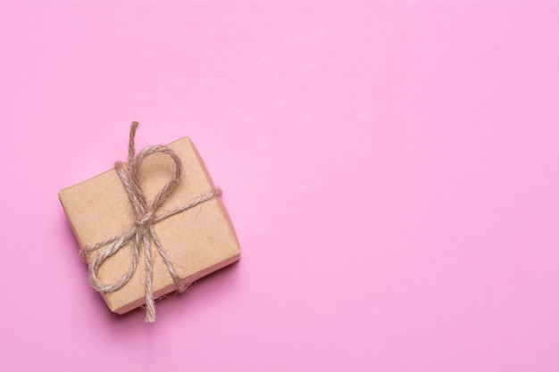 Un regalo avvolto in carta kraft su uno sfondo rosa. vista dall'alto, design piatto laico.