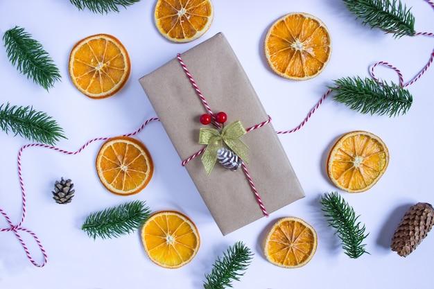 Regalo avvolto in carta kraft su uno sfondo bianco con fette d'arancia essiccate, rami di abete rosso e coni