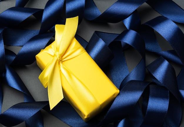 Regalo avvolto in carta gialla su sfondo blu nastro arricciato, sfondo festivo, vista dall'alto