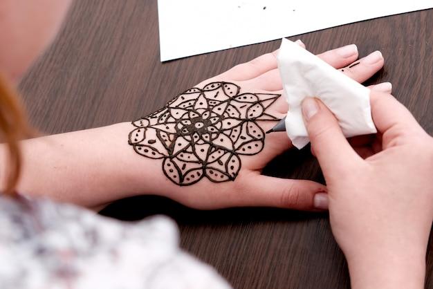 Ragazza dotata di modelli di disegno con l'henné sulle mani dei bambini durante la fiera scolastica.
