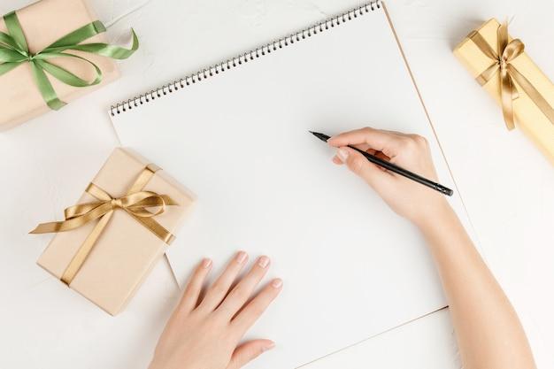 Regali sul foglio di taccuino in bianco su un muro bianco, vista dall'alto. lay piatto con copia spazio. lettera di congratulazioni con regali sul tavolo.