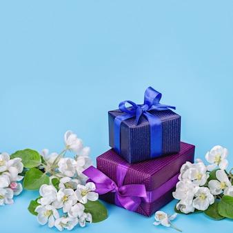 Regali in carta blu e viola, fiori bianchi di melo.