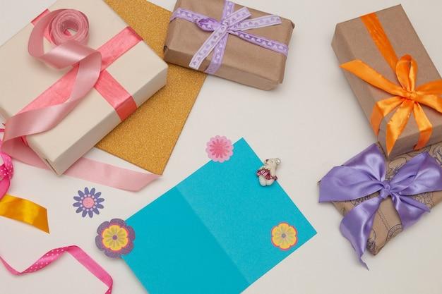 Scatole regalo con nastri luminosi e fiocchi su sfondo bianco cartolina blu, denaro, banconote da un dollaro, euro, copia posto, vista dall'alto, compleanno,