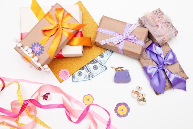 Scatole regalo con nastri luminosi e fiocchi su sfondo bianco, denaro, banconote da un dollaro, euro, spazio copia, vista dall'alto, compleanno, ringraziamento