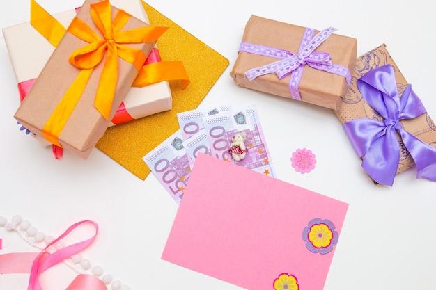 Scatole regalo con nastri luminosi e fiocchi su sfondo bianco carta rosa, denaro, banconote in dollari, euro, copia posto, vista dall'alto, compleanno,