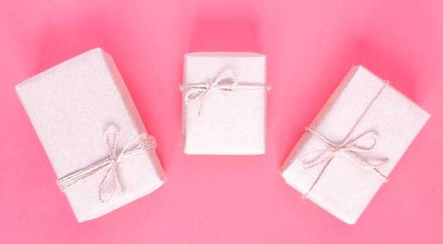 Regali in confezione artigianale ecologica per la festa su sfondo rosa.