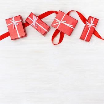 Regali o scatole regalo. scatole chiuse rosse su fondo di legno bianco.