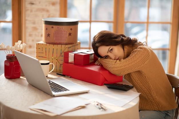 Regali pronti. giovane donna dai capelli scuri che si sente stanca dopo aver imballato i regali