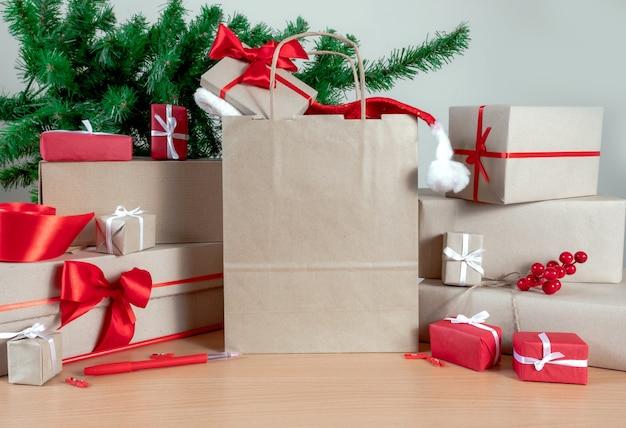 Regali, shopping bag, albero di natale e scatole di imballaggio sul tavolo, concetto di consegna.