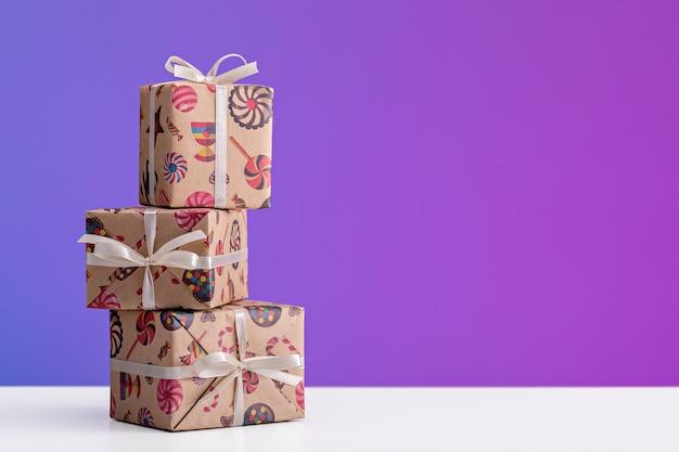 Regali e sorprese in scatole verticali, confezionate in carta natalizia. sfondo viola