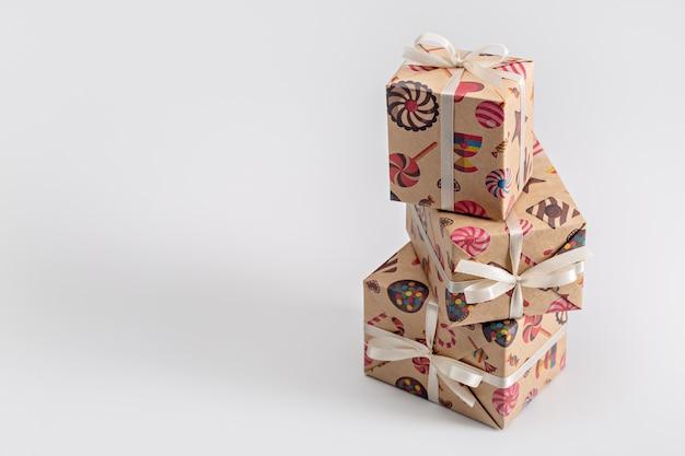 Regali e sorprese in scatole verticali, confezionate in carta natalizia.