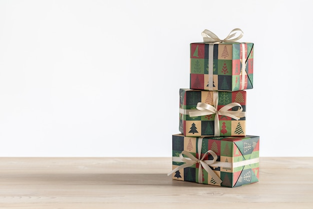 Regali in tre scatole verticali, avvolti in carta con il natale