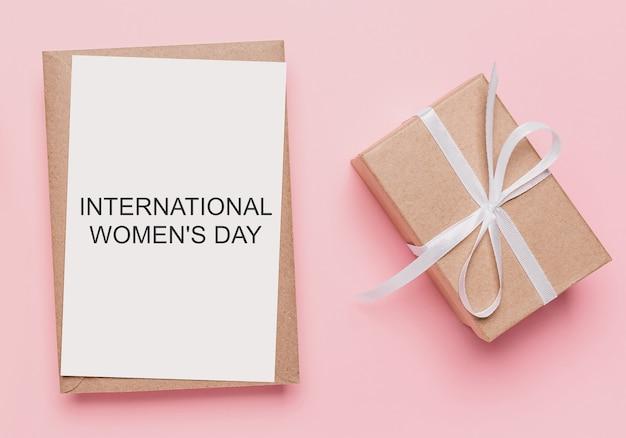 Regali con lettera nota su sfondo rosa isolato, amore e concetto di san valentino con testo giornata internazionale della donna