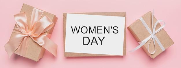 Regali con lettera nota su sfondo rosa isolato, amore e concetto di san valentino con testo festa della donna
