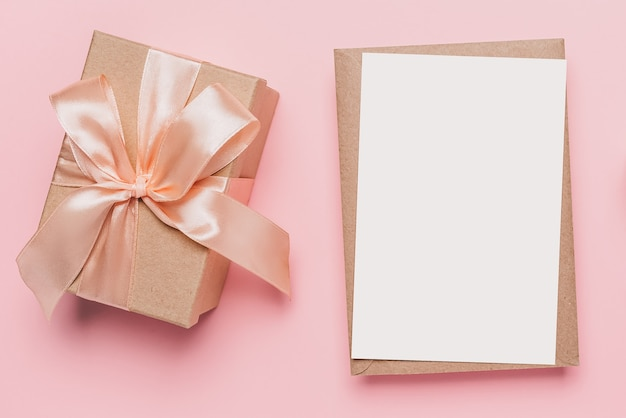 Regali con lettera di nota su sfondo rosa isolato, amore e concetto di san valentino
