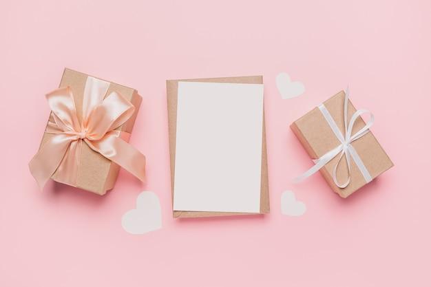 Regali con lettera nota su sfondo rosa isolato, amore e concetto di san valentino
