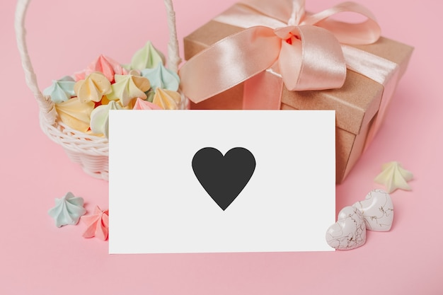 Regali con lettera nota su sfondo rosa isolato con dolci, amore e concetto di san valentino con il cuore