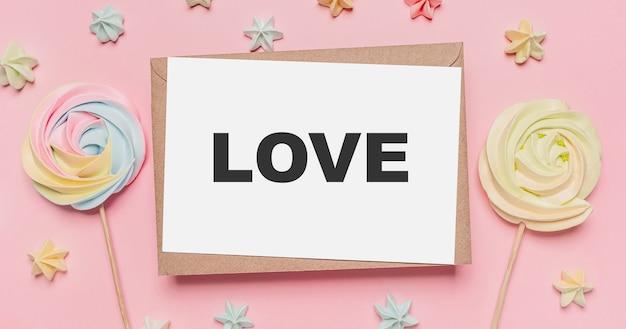 Regali con lettera nota su sfondo rosa isolato con dolci, amore e concetto di san valentino