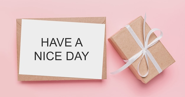 Regali con la lettera della nota sulla superficie rosa isolata con testo buona giornata