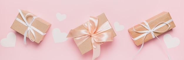 Regali con nastro wihte su sfondo rosa isolato