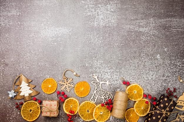 Regali avvolti in carta artigianale giocattoli di legno arance secche su sfondo grigio chiaro concetto di natale