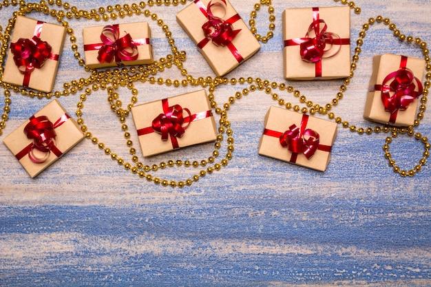 Regali avvolti in carta kraft e legati con un nastro rosso su fondo in legno. perline d'oro su sfondo blu. decorazioni festive sulla tavola.