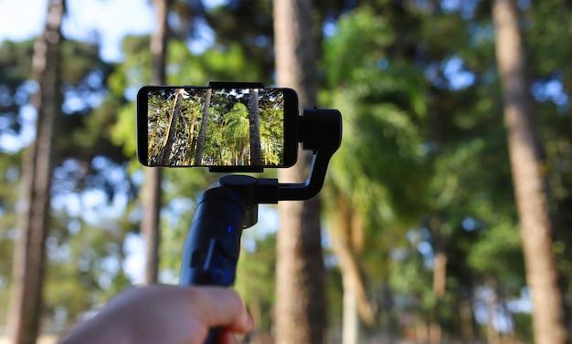 Gimbal. giovane che utilizza lo stabilizzatore per il telefono cellulare e le riprese della foresta. messa a fuoco selettiva
