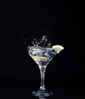 Gin tonic cocktail con spruzzi e limone su un nero isolato.