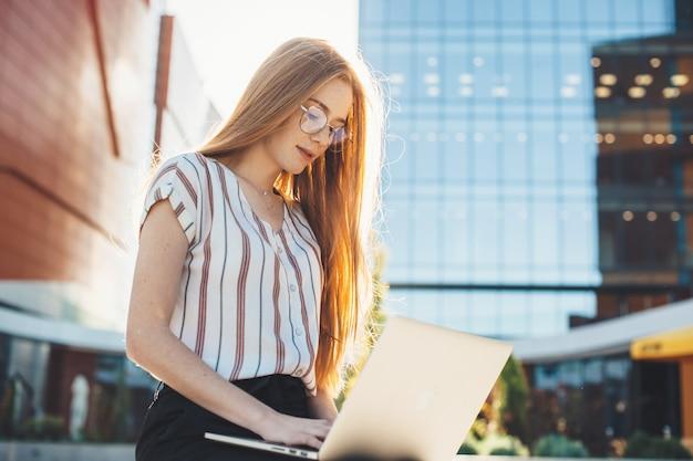 La donna di affari caucasica dello zenzero con le lentiggini e gli occhiali è seduta sulla panchina all'esterno e utilizza un computer