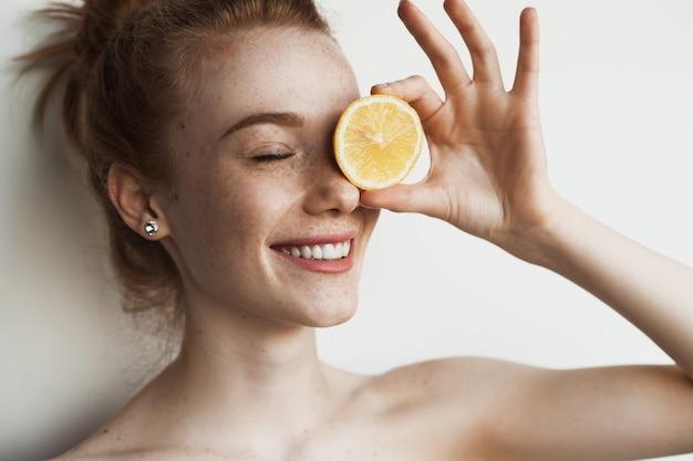 La donna caucasica dello zenzero con le lentiggini si copre gli occhi con un limone e sorride su una parete bianca dello studio