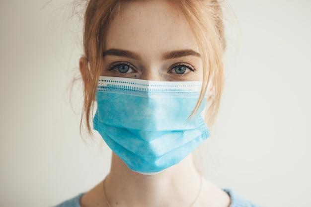 La donna caucasica allo zenzero con le lentiggini che indossa una maschera medica con filtro è in posa su una parete bianca dello studio