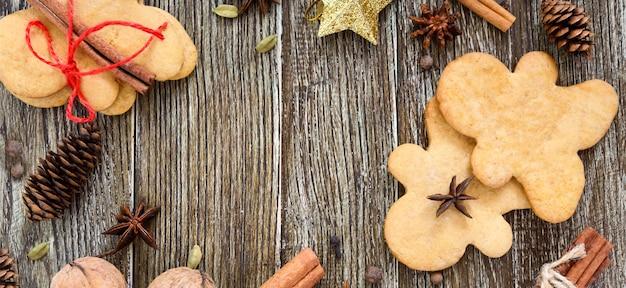 Biscotti allo zenzero su un tavolo di legno con spezie. omino di marzapane
