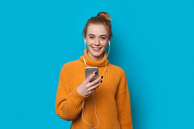 Signora allo zenzero con le lentiggini che tiene un telefono e ascolta la musica mentre sorride sulla parete blu