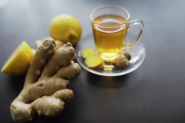Radice di zenzero intera e affettata. tè allo zenzero con limone sullo sfondo scuro. radice di zenzero fresco su sfondo di pietra. vitamine. vista dall'alto. spazio libero per il tuo testo.