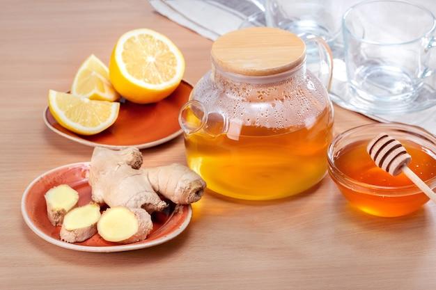 Concetto di ingredienti del tè allo zenzero. teiera con tè caldo sulla tavola di legno.