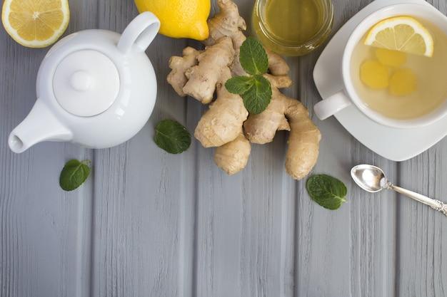 Tè allo zenzero e ingredienti su fondo di legno grigio.vista dall'alto.copia dello spazio.